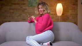Hübsche Hausfrau in der rosa Strickjacke, die bescheiden im Profil auf Sofa mit Smartphonelächeln zur Kamera in der Hauptatmosphä stock video