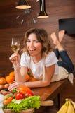 Hübsche Hausfrau, die auf dem Tisch mit Glas Wein liegt Stockfoto