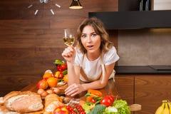 Hübsche Hausfrau, die auf dem Tisch mit Glas Wein liegt Stockbilder