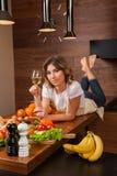 Hübsche Hausfrau, die auf dem Tisch mit Glas Wein liegt Lizenzfreies Stockfoto