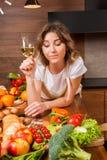 Hübsche Hausfrau, die auf dem Tisch mit Glas Wein liegt Stockfotos