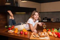 Hübsche Hausfrau, die auf dem Tisch mit Glas Wein liegt Lizenzfreie Stockfotos