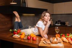 Hübsche Hausfrau, die auf dem Tisch mit Glas Wein liegt Lizenzfreie Stockfotografie