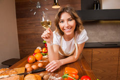 Hübsche Hausfrau, die auf dem Tisch mit Glas Wein liegt Stockbild