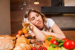 Hübsche Hausfrau, die auf dem Tisch mit Glas Wein schläft Stockbilder