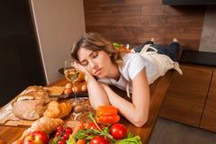 Hübsche Hausfrau, die auf dem Tisch mit Glas Wein schläft Stockfoto