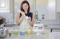 Hübsche Hausfrau, die kleine Kuchen macht Lizenzfreie Stockfotos