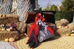 Hübsche Hexe, die auf einem alten Kasten mit Gold sitzt Stockfotografie