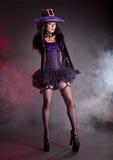 Hübsche Hexe in purpurrotem und schwarzem gotischem Halloween-Kostüm Lizenzfreie Stockfotos