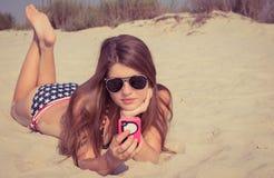 Hübsche Jugendliche in der Sonnenbrille, die auf dem Strand mit intelligentem liegt Lizenzfreies Stockbild