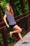 Hübsche Jugendliche, die auf einer Brücke sich entspannt Stockfotos