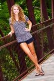 Hübsche Jugendliche, die auf einer Brücke steht Stockbild