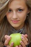 Hübsche Jugendliche, die einen Apfel anhält Stockbild