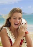 Hübsche Jugendliche, die zu einem Seashell hört Lizenzfreies Stockfoto