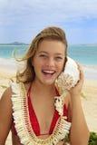 Hübsche Jugendliche, die zu einem Seashell hört Stockfoto