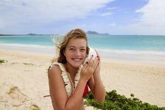 Hübsche Jugendliche, die zu einem Seashell hört Stockbild