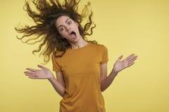Hübsche junge überraschte Frau mit dem gelockten fliegenden Haar, kippt sie glücklich von etwas, glaubt, lokalisiert über Gelb lizenzfreie stockfotografie