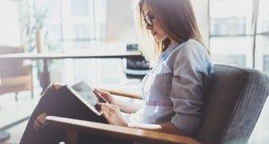 Hübsche junge blonde tragende Gläser und Anwendung des elektronischen Notentablet-computers auf sonnigem Arbeitsplatz horizontal  Lizenzfreie Stockfotos