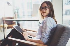 Hübsche junge blonde tragende Gläser und Anwendung des elektronischen Notentablet-computers auf sonnigem Arbeitsplatz horizontal  Stockfotos