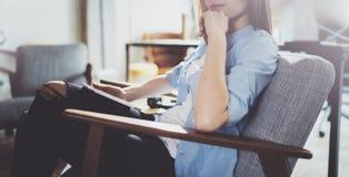 Hübsche junge blonde tragende Gläser und Anwendung des elektronischen Notentablet-computers auf sonnigem Arbeitsplatz horizontal  Lizenzfreies Stockbild