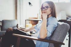 Hübsche junge blonde tragende Gläser und Anwendung des elektronischen Notentablet-computers auf sonnigem Arbeitsplatz horizontal  Stockfoto