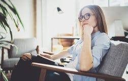 Hübsche junge blonde tragende Gläser und Anwendung des elektronischen Notentablet-computers auf sonnigem Arbeitsplatz horizontal  Lizenzfreie Stockfotografie
