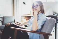 Hübsche junge blonde tragende Gläser und Anwendung des elektronischen Notentablet-computers auf sonnigem Arbeitsplatz horizontal  Lizenzfreie Stockbilder