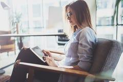 Hübsche junge blonde tragende Gläser und Anwendung des elektronischen Notentablet-computers auf sonnigem Arbeitsplatz horizontal  Stockfotografie