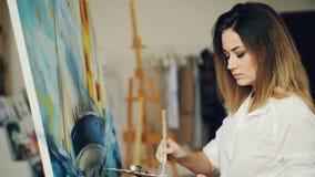 Hübsche junge Dame ist bemüht, Bild in der Werkstatt unter Verwendung der hellen Farbe und der befleckten Palette zu malen Mädche stock video
