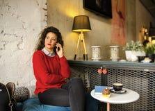 Hübsche junge erwachsene Frau, die in der Kaffeestube sitzt stockbilder