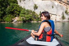 Hübsche, junge Frau auf einem Kanu auf einem See, schaufelnd Lizenzfreies Stockfoto