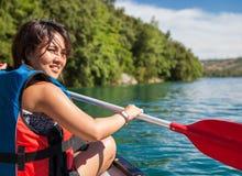 Hübsche, junge Frau auf einem Kanu auf einem See, schaufelnd Stockfotos