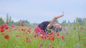 Hübsche junge Frau, die in ein Mohnblumenfeld glücklich lächelt läuft und tanzt Verbindung mit Natur Freizeit in der Natur stock video footage