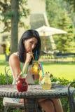 Hübsche junge Frau, die frische Limonade im Garten, Produktfotografie für Restaurant, frische Limonade des Sommers trinkt lizenzfreie stockfotos