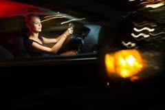 hübsche, junge Frau, die ihr modernes Auto nachts, in einer Stadt fährt Stockfotografie