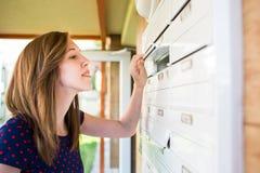 Hübsche, junge Frau, die ihren Briefkasten überprüft Stockbild
