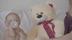 Hübsche junge Frau, die mit ihrem Baby sitzt, das, spielend mit der Babyflasche, die im Bett sitzt, gebotener Spielzeugbär nah is stock video