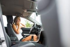 Hübsche, junge Frau in ihrem modernen Auto um ihr Anruftelefon ersuchend Lizenzfreie Stockbilder
