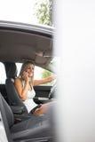 Hübsche, junge Frau in ihrem modernen Auto um ihr Anruftelefon ersuchend Stockfotos