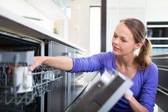 Hübsche, junge Frau in ihrer modernen und gut ausgerüsteten Küche lizenzfreies stockbild