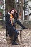 Hübsche junge Frau im schwarzen Mantel und bunter Schal sitzen auf Holzbank in Park winte stockfotos