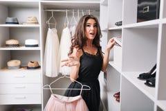 Hübsche junge Frau mit dem überraschten Blick stehend in der netten Garderobe, interessiert, was innerhalb des Kastens ist, rosa  stockbild