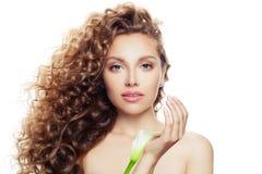 Hübsche junge Frau mit dem langen gelockten Haar, klarer Haut und Lilienblume in ihren Händen lokalisiert auf Weiß stockfoto