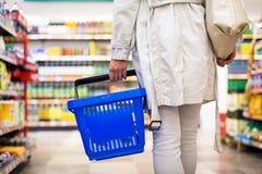 Hübsche, junge Frau mit kaufenden Lebensmittelgeschäften eines Einkaufskorbs Lizenzfreie Stockfotos