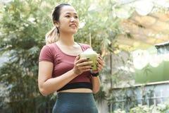 Hübsche junge Frau mit Kokosnusscocktail stockfotos