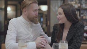 Hübsche junge Frau und hübscher bärtiger blonder ein Mann, der am Tisch sitzt Der Mann, welche seiner Freundin guten Wörtern sagt stock video footage