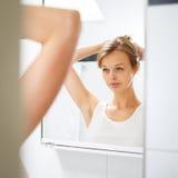 Hübsche, junge Frau vor ihrem Badezimmerspiegel Stockbilder