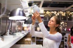Hübsche, junge Frau, welche die rechte Lampe wählt Lizenzfreie Stockfotografie