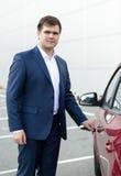 Hübsche junge Geschäftsmannöffnungs-Autotür Lizenzfreie Stockfotografie