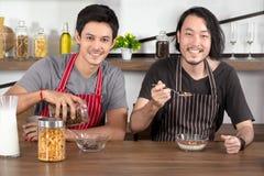Hübsche junge Männer, die Frühstück, ein strömendes Getreide des Mannes in Glasschüssel und den anderen haltenen Löffel im modern lizenzfreie stockfotos